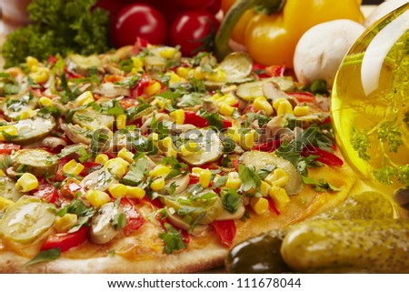 Pizza with pickles, corn, pepper and cheese and ingredients - stock photo