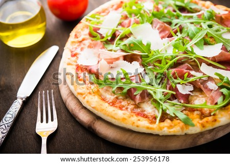 Pizza with prosciutto (parma ham), arugula (salad rocket) and parmesan on dark wooden background close up. Italian cuisine. - stock photo