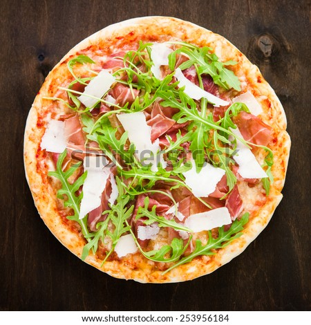 Pizza with prosciutto (parma ham), arugula (salad rocket) and parmesan on dark wooden background top view. Italian cuisine. - stock photo