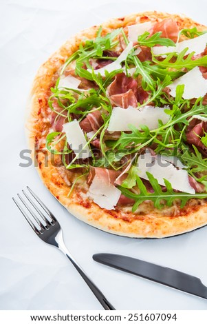 Pizza with prosciutto (parma ham), arugula (salad rocket) and parmesan on white background top view. Italian cuisine. - stock photo