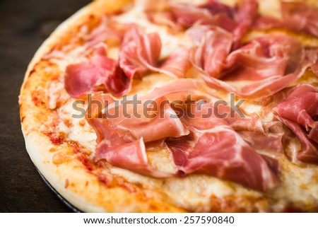 Pizza with prosciutto (parma ham) on dark wooden background close up. Italian cuisine. - stock photo