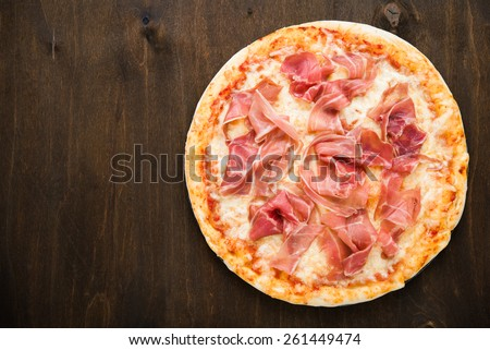Pizza with prosciutto (parma ham) on dark wooden background top view. Italian cuisine. Space for text. - stock photo