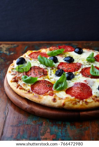 Pizza with salami, black olives and herbs