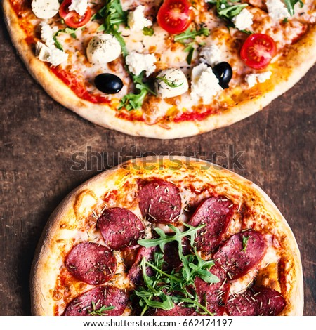 Pizza with salami, olives and cheese on a rustic wooden table flat lay photo
