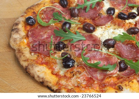 Pizza with salami, olives and rocket