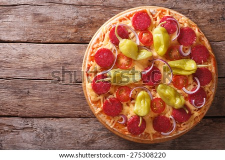 pizza with salami, pepperoni peppers, tomatoes and onions on a table close-up vertical view from above, rustic