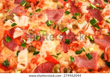 Pizza with salami, sausage, ham, green olives, red pepper, cucumber, pineapple and greens close-up, selective focus, macro - stock photo