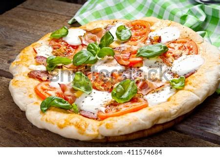 Pizza with salami, tomato and ham - stock photo