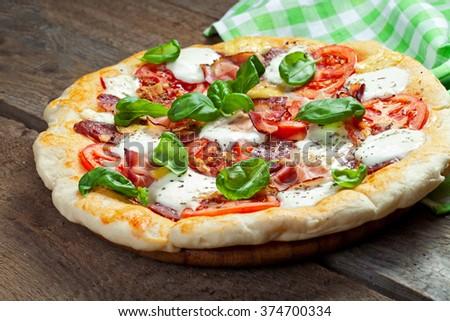Pizza with salami, tomato and hamv - stock photo