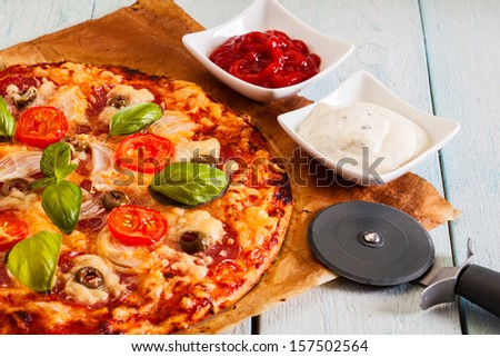 Pizza with salami, tomatoes and olives on table
