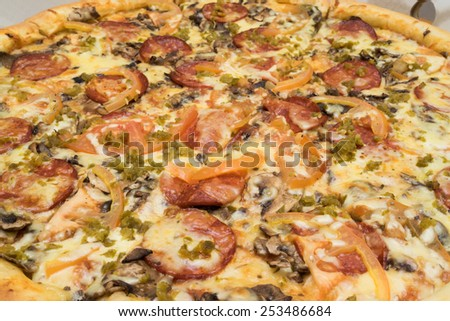 pizza with sausages, tomatoes and spinach close up view - stock photo