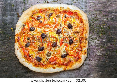 Pizza with sliced vegetables on rustic, vintage style wood background