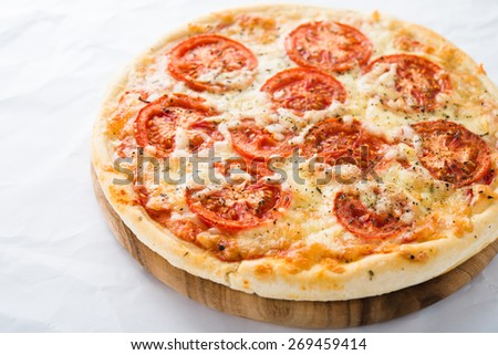 Pizza with tomato, cheese and dry basil on white background close up. Italian cuisine. - stock photo