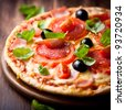 Pizza with tomato, salami and olives - stock photo