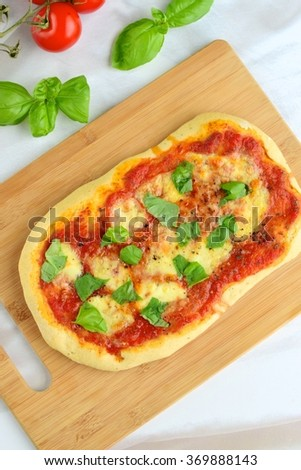 pizza with tomato sauce, mozzarella and basil leaves on wooden board