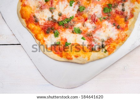 pizza with tomatoes, basil, capers and  mozzarella,homemade, close up - stock photo