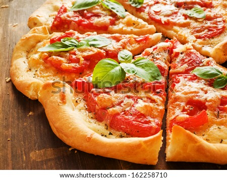 Pizza with tomatoes, cheese, herbs and baby basil. Shallow dof.