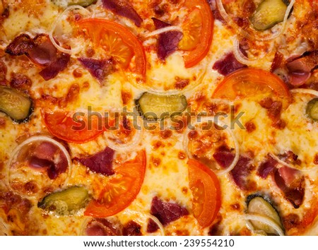 Pizza with tomatoes, onions, bacon and pickles