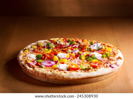 pizza with vegetables on wooden background - stock photo