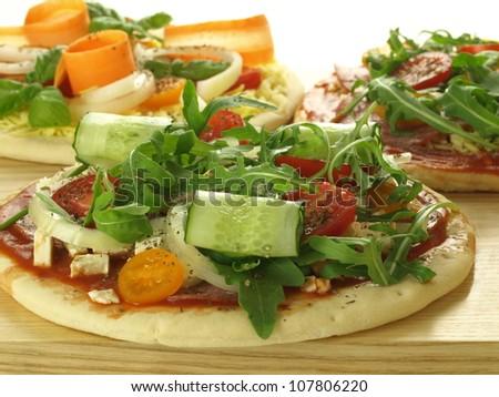 Pizza with veggies: arugula, cucumber, tomatoes and onion - stock photo
