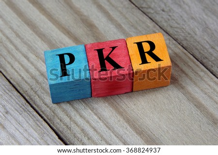 PKR (Pakistani Rupee) sign on colorful wooden cubes