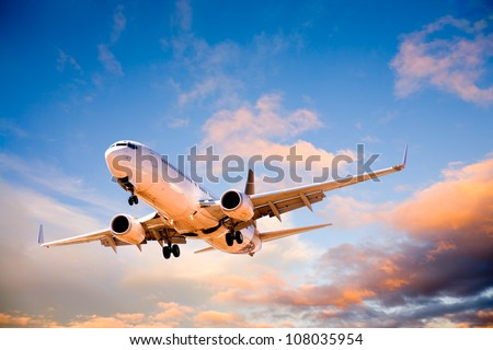Place flying in sunset sky. - stock photo