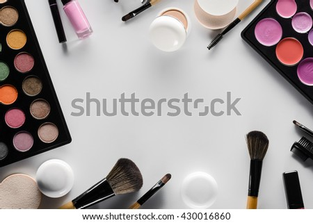 Place for lettering in the center of the picture with different cosmetics: concealers for hiding the defects of skin, colorful lipstick and eyeshadow palettes for make-up and brushes. - stock photo