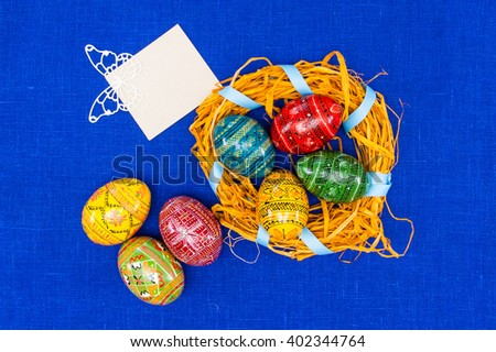Place for text.greeting easter card,easter eggs in nest in textile blue background - stock photo