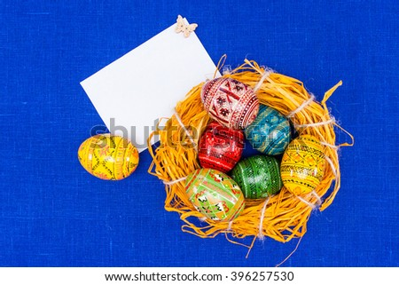Place for text.greeting easter card,easter eggs in nest in textile blue background.  Your text here - stock photo