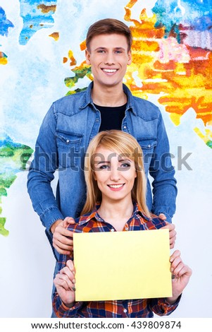 Place for your advertising! Two models hold frame with copyspace in front of wall. - stock photo