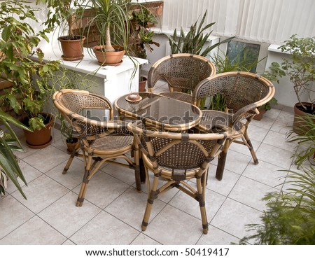 Place in the garden office for meetings. Rattan furniture is buried in the green pot plants. - stock photo