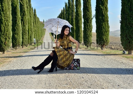 Place of destination. Stylish young woman with the white umbrella  sits on the suitcase on a rural road along cypress alley. Tuscan, Italy - stock photo