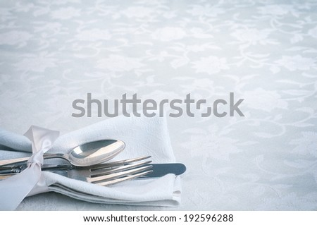 Place setting Closeup with fork, knife, spoon, white napkin in lower left on damask tablecloth background with room or space for copy, text.  Horizontal, vintage blue toned - stock photo