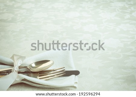 Place setting Closeup with fork, knife, spoon, white napkin in lower left on damask tablecloth background with room or space for copy, text.  Horizontal, green tone vintage - stock photo