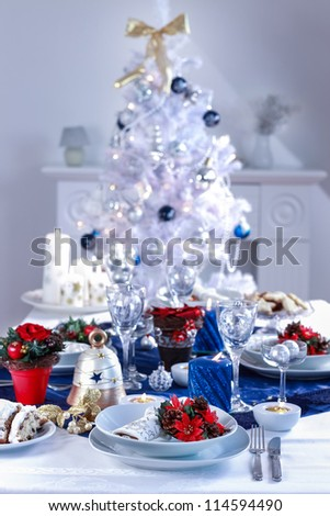 Place setting for Christmas in white and blue with the tree - stock photo