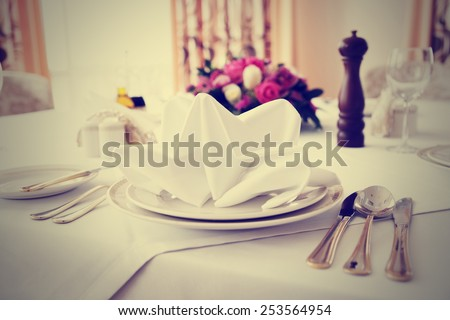 Place setting in an expensive haute cuisine restaurant, toned image - stock photo
