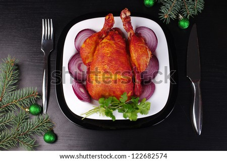 Place setting including one white dinner plate with grilled chicken on a black table - stock photo