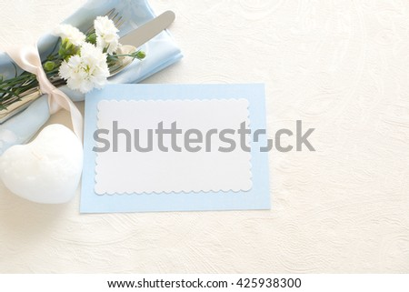Place setting of Silverware, blue napkin, blank name card, heart shaped candle and carnations on side on off white tablecloth with room or space for copy, text, your words. Horizontal top aerial view