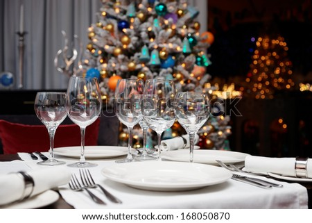 Place setting with Christmas tree in background, shallow focus depth - stock photo