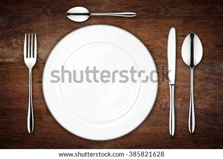 place setting with empty dish fork spoon and knife on wooden background - stock photo
