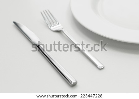 Place setting with empty plate, knife and fork - stock photo