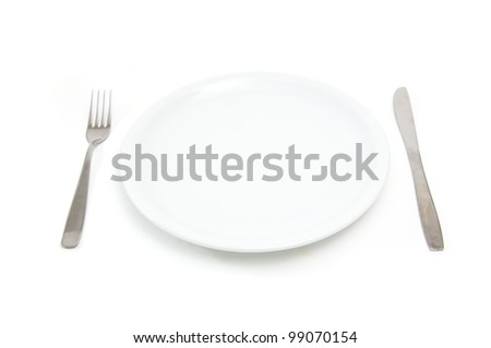 Place setting with empty white plate, knife and fork - stock photo