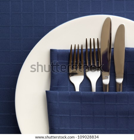 Place setting with knives and forks in dark blue napkin, over matching tablecloth.  White plate. - stock photo