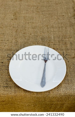 Place setting with plate and fork against brown plate mat - stock photo