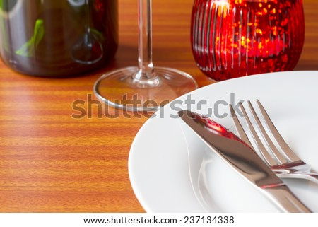 Place setting with red candle on wooden table