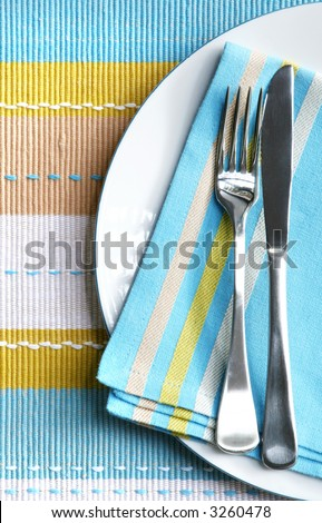 Place setting with silver fork and knife on pastel napkin, and matching placemat.  Vertical view. - stock photo