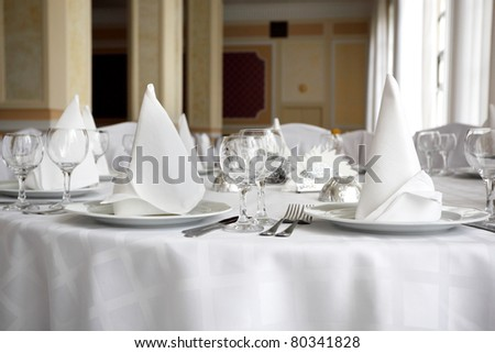 Place settings on an elegant, white dining table in a restaurant.