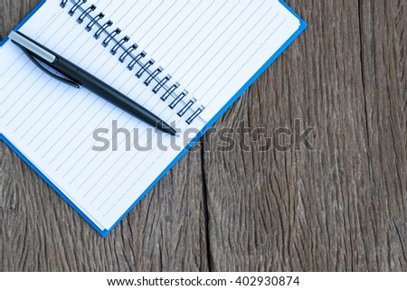 Place the pen on a blank page of a notebook on old wooden background. - stock photo