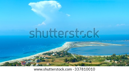 Place, where unite sky, sea and horizont mountain. Beautiful summer Lefkada coast beach and kiteboarders (Greece, Ionian Sea,  view from up). All people are not identifiable. - stock photo