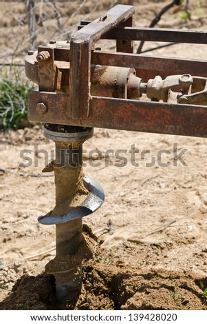 placed in a tractor auger making a hole